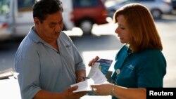 Una promotora de salud habla con un hombre sobre el Obamacare en Los Ángeles.