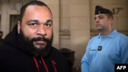 French controversial humorist Dieudonne Mbala Mbala arrives for a trial at the Paris courthouse on December 13, 2013 on the charges of defamation, insults, incentive to hate and discrimination.