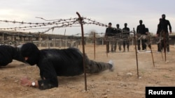 FILE - Islamist fighters crawl under razor wire at a training camp in near Damascus in this 2013 photo.