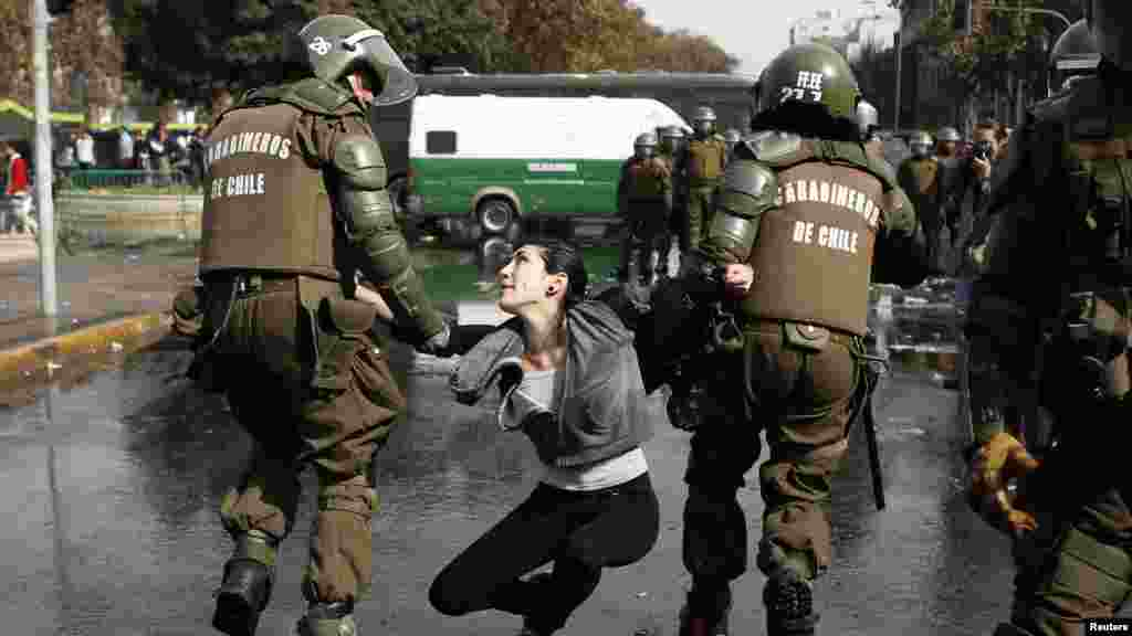 A demonstrator is detained during May Day rallies in Santiago, Chile May 1, 2013.