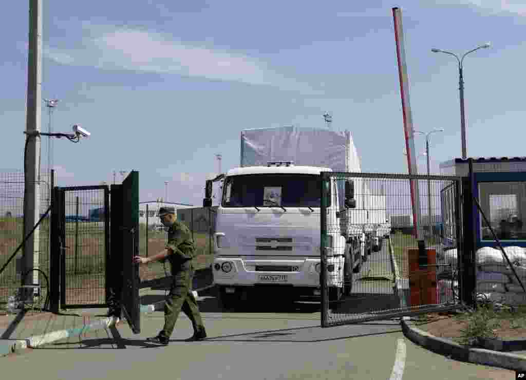 A Russian guard opens a border gate for passage into Ukraine for the first trucks heading into the country from the Russian town of Donetsk, Rostov-on-Don region, Russia, Aug. 22, 2014.