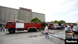 """Mobil pemadam kebakaran terlihat parkir di depan pabrik pembuatan lemari pendingin """"Weng"""" di distrik Baoshan, Shanghai (31/8)."""