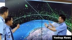 한국 공군이 8일 충남 계룡대에 있는 공군연구단 건물에 우주정보상황실을 개관했다. 공군 관계자들이 상황실 모니터에 표시되는 지구 주변을 도는 인공위성과 파편 등에 대한 정보를 살펴보고 있다.