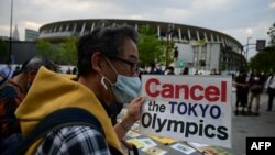 FILE - People take part in a protest against the hosting of the 2020 Tokyo Olympic Games outside the Olympic museum in Tokyo on May 9, 2021. (AFP)