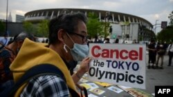 People take part in a protest against the hosting of the 2020 Tokyo Olympic Games outside the Olympic museum in Tokyo on May 9, 2021. (Photo by Philip FONG / AFP)