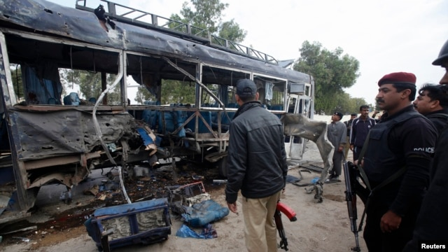 Security officials stand near a damaged police bus at the site of an explosion in Karachi, Feb. 13, 2014.