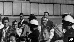ປະທານາທິບໍດີ ຈອນເຄເນດີ (ຂວາ) ກໍາລັງນັ່ງລົດໄປກັບພັນລະຍາ ຂອງເພິ່ນ (ຊ້າຍ) ແລະຜູ້ວ່າການລັດເທັກຊັສ ໃນລົດທີ່ເປີດຫລັງຄາ ໃນເວລາທີ່ທ່ານຖືກລອບສັງຫານທີ່ເມືອງ ດາລາສ ລັດເທັກຊັສ ໃນວັນທີ 22 ພະຈິກ, 1963 (AP Photo, file)