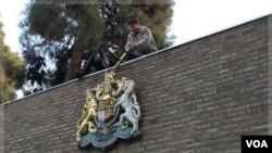 Warga Iran berusaha memindahkan lambang negara Inggris dari gedung Kedutaan Inggris di Teheran (29/11). Hubungan Inggris dan Iran tegang sejak penyerbuan Kedutaan Inggris di Teheran November lalu.