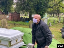 Yilma Asfaw grieving at the funeral of his wife, Wegene Debele of Takoma Park, Maryland. Theyhave been together for 25 years. Shewas eight months pregnant when she contracted the coronavirus.