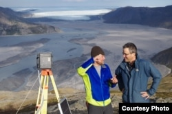 UCLA geography graduate student Lincoln Pitcher, left, and UCLA geography professor Laurence C. Smith overlook the Isortoq River, where meltwater leaves the Greenland ice sheet to flow to the ocean seen in the distance. (UCLA/Lawrence C. Smith)