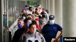FILE - Job seekers line up outside a Career Center in Frankfort, Kentucky, June 18, 2020.