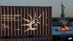 Sebuah peti kemas yang membawa replika Patung Liberty, kiri, melintas di depan Patung Liberty berukuran penuh saat tiba dari Perancis dengan kapal kontainer di New York, Rabu, 30 Juni 2021. (Foto: AP)