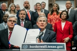 """Gov. Greg Abbott speaks during a press conference on details of his plan for Texas to build a border wall and provide $250 million in state funds as a """"down payment."""", June 16, 2021 in Austin, Texas."""