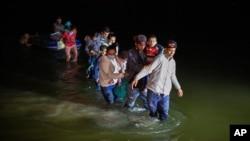 Porodice migranata, uglavnom iz zemalja Srednje Amerike, koračaju kroz vodu nakon što su ih krijumčari isporučili na malim splavovima na napuhavanje na tlo SAD-a u Romi, Teksas, 24. marta 2021. godine.