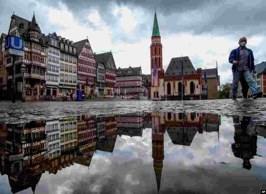 انعکاس ساختمانهای میدان رومربرگ در آب جمع شده در یک گودال بعد از بارش باران در فرانکفورت، آلمان