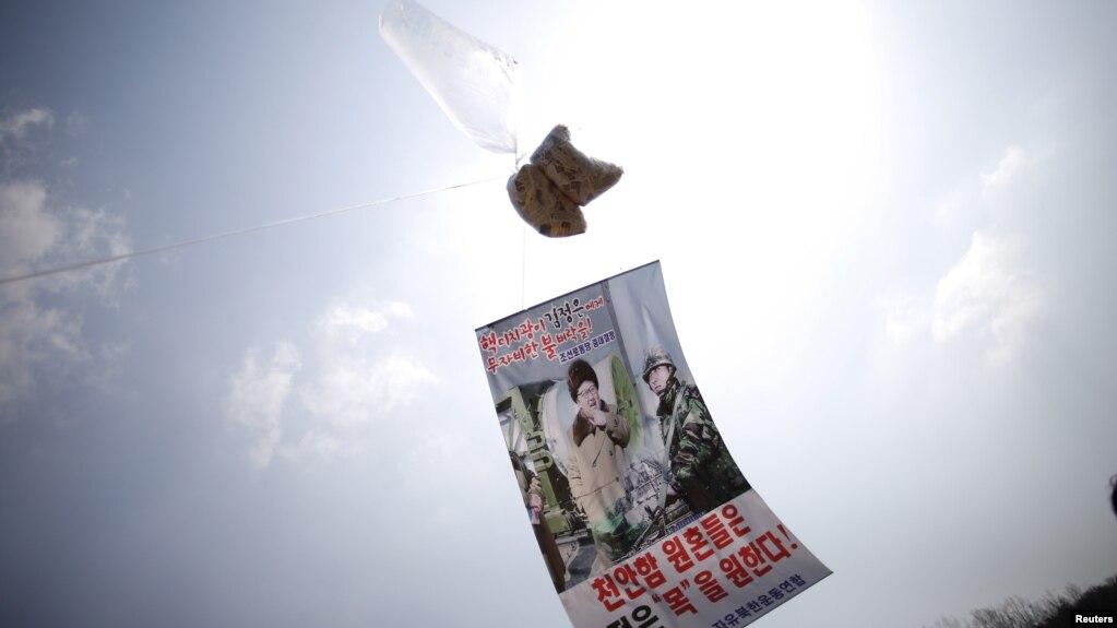 2016年3月26日,在分隔韩朝非军事区附近上空的一个气球系着谴责朝鲜领导人金正恩的传单。(photo:VOA)