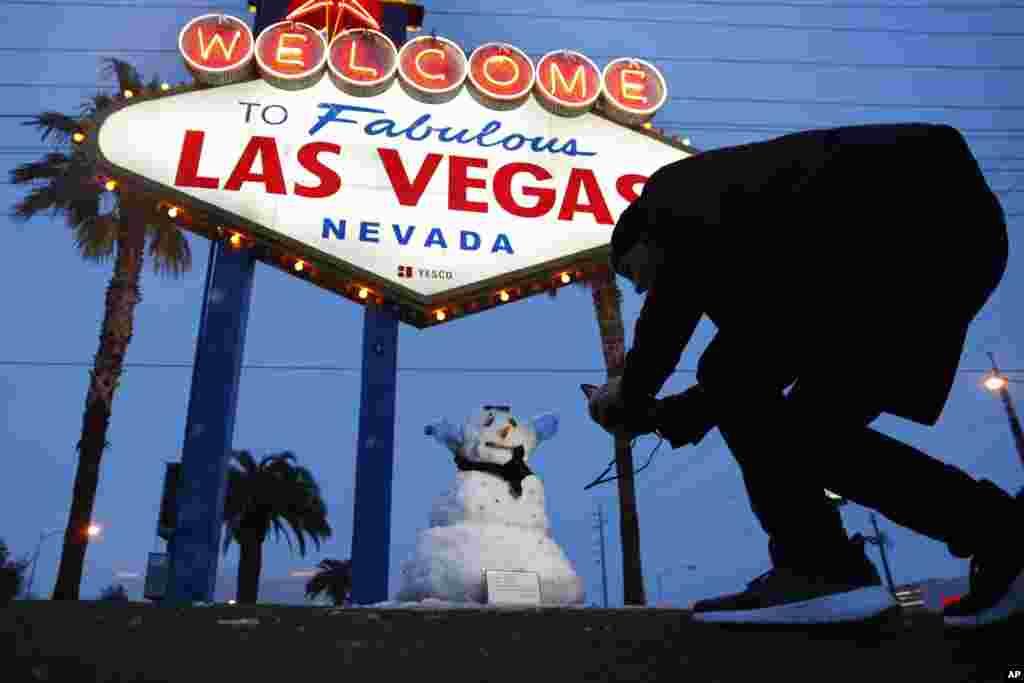 لاس وگاس در غرب آمریکا معمولا شاهد بارش برف نیست، حالا که برف آمده، این مرد از یک آدم برفی عکس می گیرد.