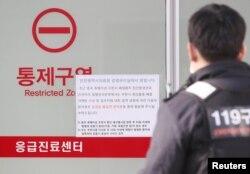一名韩国救护人员走过医院墙上张贴的警示武汉肺炎的通知,这所医院收治了一名来自武汉感染了新型冠状病毒的中国妇女。(2020年1月20日)