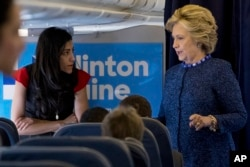 FILE - Democratic presidential candidate Hillary Clinton speaks with senior aide Huma Abedin aboard her campaign plane at Westchester County Airport in White Plains, Oct. 28, 2016.