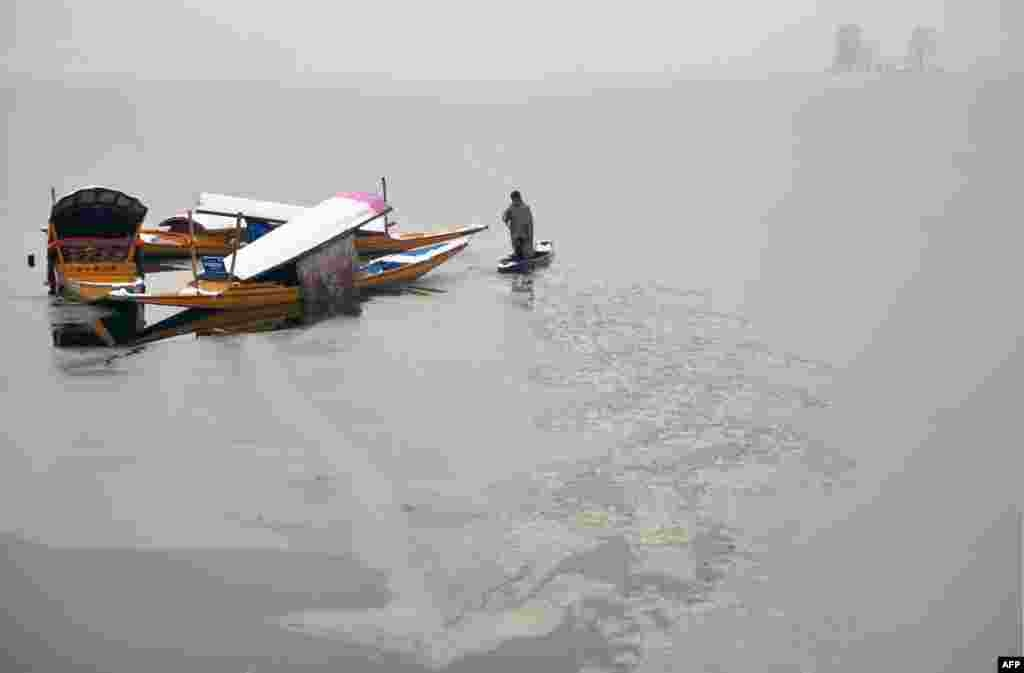 A Kashmiri boatman uses his oar to break the ice layer of the frozen Dal Lake after a heavy snowfall in Srinagar.