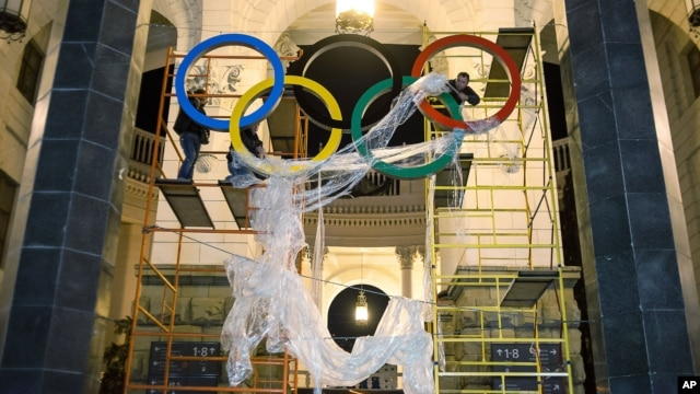 In this Oct. 28, 2013 photo, workers fix the Olympic emblem at an entrance to the railway station of Russia's Black Sea resort of Sochi.