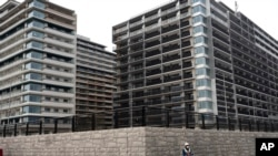 FILE - A guard stands in front of apartment buildings at the Athletes Village for the Tokyo 2020 Olympics, in Tokyo, March 23, 2020.