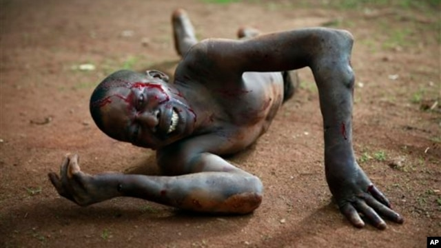 Kevin, a man accused of being a thief by civil servants at the Work Inspection office, lies in pain after being attacked by a man with a machete and sticks in plain view of others in Bangui, Central African Republic, April 18, 2014.