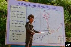 지난 24일 북한 풍계리 핵실험장에서 북한 당국자가 갱도와 관련 시설의 폐기 방법과 순서를 설명하고 있다.