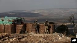 Dua tentara Turki memantau situasi di Afrin, Suriah dari bukit Bursayah (3/3).