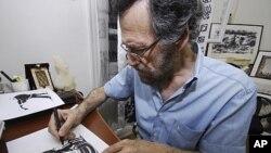 图为卡通漫画家阿里.费尔扎特8月14日在叙利亚的大马士革工作资料照