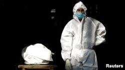 បុគ្គលិកសុខាភិបាលម្នាក់ពាក់ឧបករណ៍ការពារខ្លួន PPE ឈរជិតសាកសពរបស់មនុស្សម្នាក់ ដែលស្លាប់ដោយសារជំងឺកូវីដ១៩ នៅទីក្រុងញូវដេលី ប្រទេសឥណ្ឌា ថ្ងៃទី ២៨ ខែកញ្ញា ឆ្នាំ២០២០។