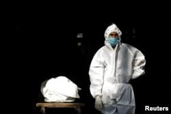 Seorang nakes di India, mengenakan alat pelindung diri (APD), berdiri di samping jenazah seorang pria yang meninggal akibat penyakit COVID-19, sebelum dikremasi di sebuah krematorium di New Delhi, India, 28 September 2020.