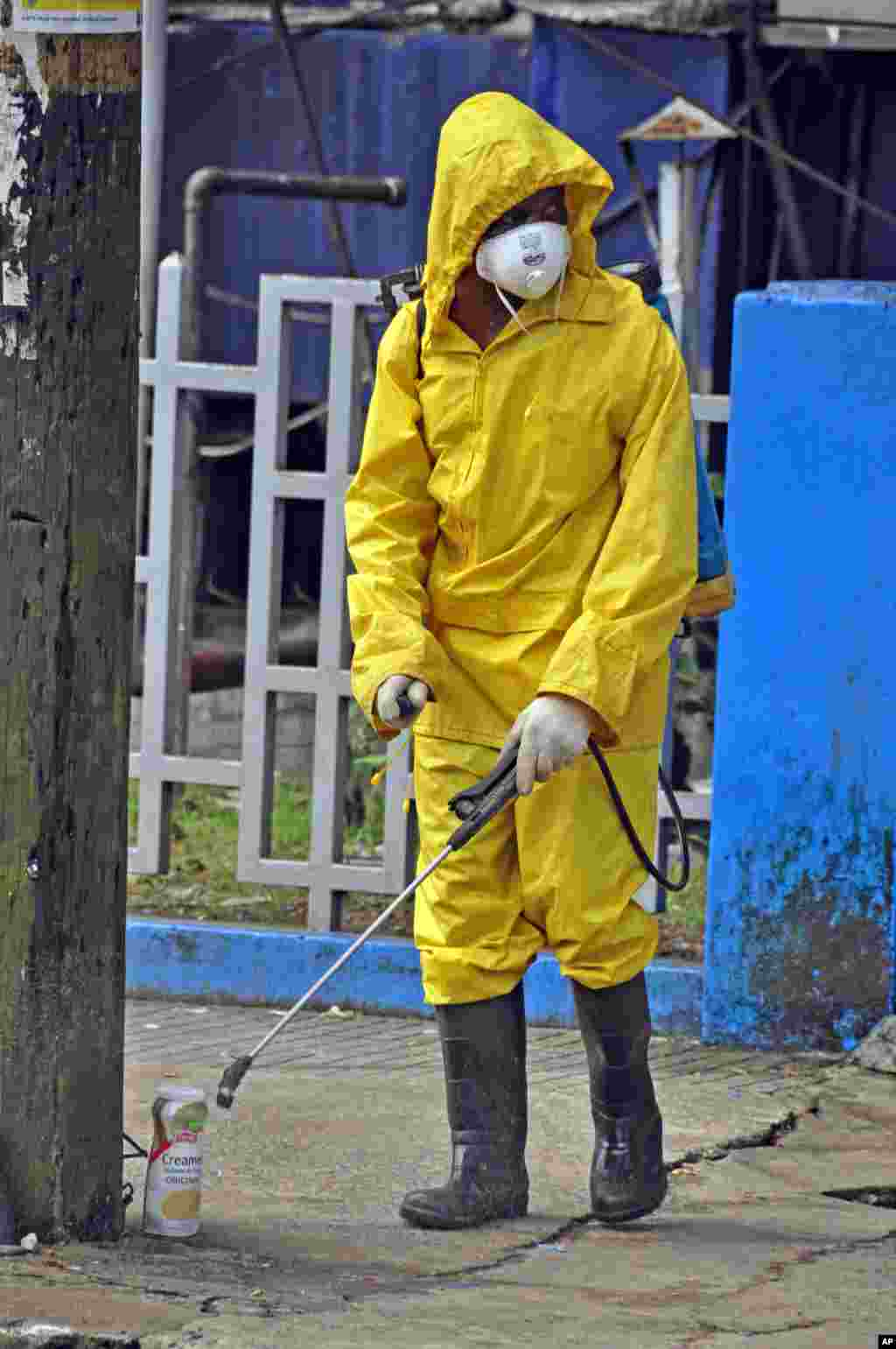 An employee of the Monrovia City Corporation sprays disinfectant along the streets to prevent the spread of the deadly Ebola virus, Monrovia, Liberia, August 1, 2014.