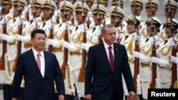 Turkey's President Recep Tayyip Erdogan, right, and his Chinese President Xi Jinping inspect honor guards during a welcoming ceremony outside the Great Hall of the People in Beijing, July 29, 2015.