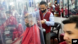Peter Shamuelov, center, wears a protective mask as he gives a haircut to a customer at Ace of Cuts barbershop, Monday, June 22, 2020, in New York. For the first time in three months, New Yorkers will be able to dine out, though only at outdoor tables. (A