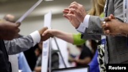 Corporate recruiters (R) shake hands as they talk with job seekers at a Hire Our Heroes job fair targeting unemployed military veterans and sponsored by the Cable Show, a cable television industry trade show in Washington, June 11, 2013.