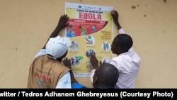 Une équipe de l'OMS colle une affiche de sensibilisation à l'épidémie d'Ebola, Beni, Nord-Kivu, RDC, le 15 octobre 2018. (Twitter/Tedros Adhanom Ghebreyesus)