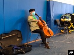 This photo provided by Berkshire Community College shows cellist Yo-Yo Ma performing at Berkshire Community College's second dose Pfizer vaccination clinic in the Paterson Field House on March 13, 2021 in Pittsfield, Mass.