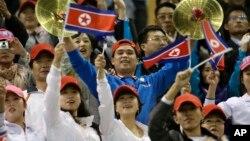 10일 중국 텐진에서 열리고 있는 제6회 동아시아경기대회 남자 축구 경기에서, 북한 응원단이 선수들을 응원하고 있다.