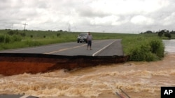 A motorist stands on the edge of a break in highway BR 356 that was washed away after several days of heavy rains swelled the Muriae River in Campos, 230 kms (142 miles) northeast of Rio de Janeiro, January 5, 2012.