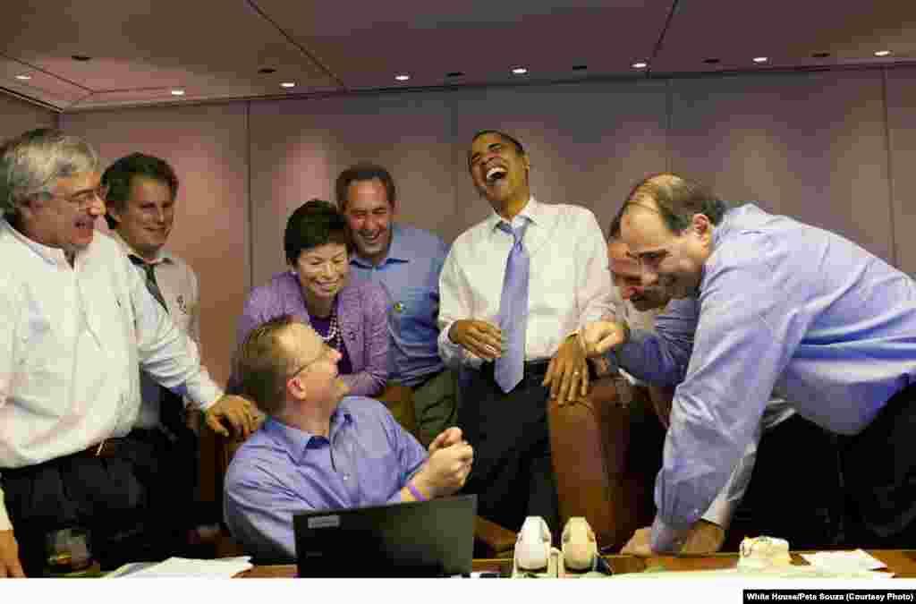 Le responsable de la presse montre au président les différentes chemises choisies par les pays d'accueil du sommet des Amériques. Il a répondu vouloir l'accueillir à Hawaï pour imposer la chemise hawaïenne, le 14 novembre 2009. (White House/Pete Souza)