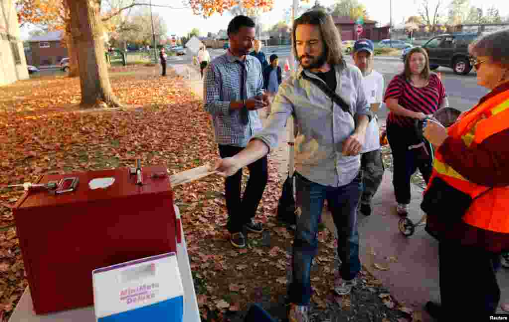 An Obama supporter casts his ballot early at an outdoor ballot box in Denver, Colorado October 30, 2012.