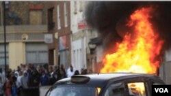 Sebuah mobil di belakang taksi di gambar ini dibakar oleh massa di Hackney, London timur, Senin (8/8).