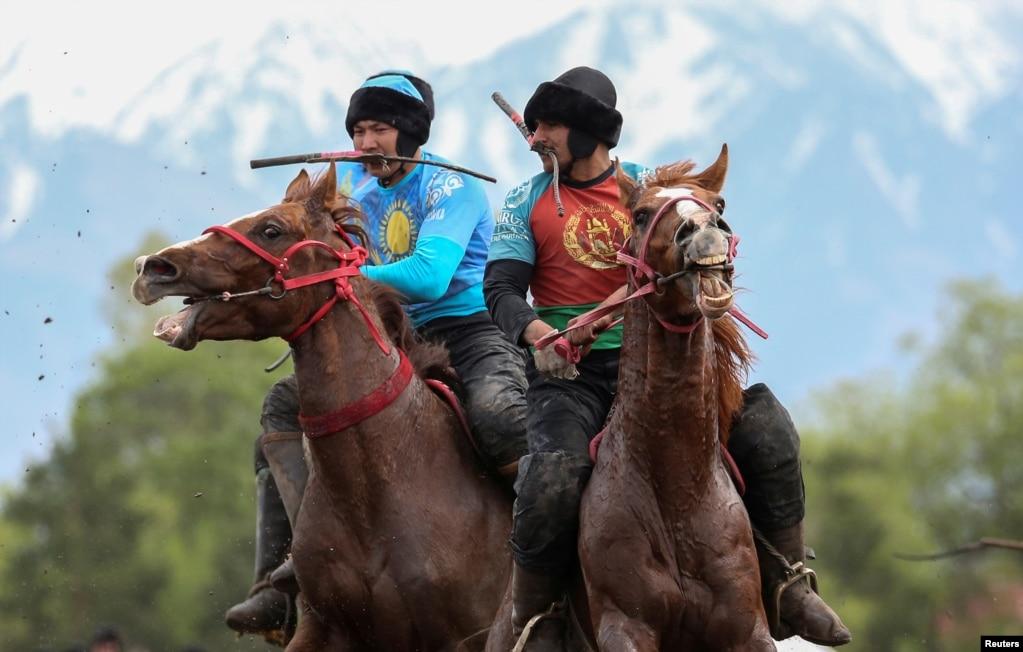 Всадники играют в кокпар, традиционную игру между двумя командами, конкурирующими, чтобы бросить манекен козы в круг забивания, во время первого азиатского чемпионата по конному спорту, недалеко от Алматы, Казахстан.