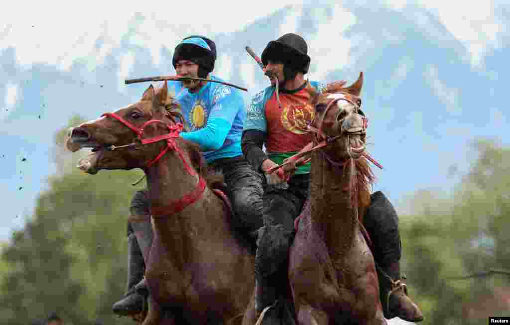 Horsemen play Kokpar, a traditional game between two teams competing to throw the dummy of a goat into a scoring circle, during the first Asian Equestrian Championship, near Almaty, Kazakhstan.