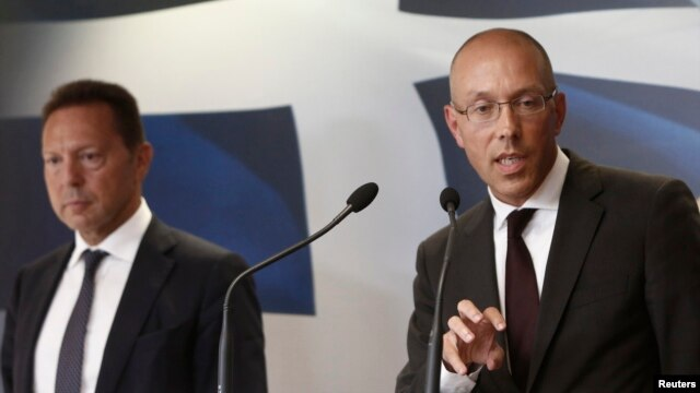 European Central Bank (ECB) executive board member Joerg Asmussen (R) addresses reporters next to Greece's Finance Minister Yannis Stournaras during a news conference in Athens, Aug. 21, 2013.