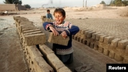 FILE - Children work at a brick-making factory in Jalalabad, Dec. 17, 2013.