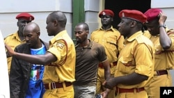 Rwandan citizen Muhamoud Mugisha, right, and his co-accused Ugandan Edris Nsubuga, left, leave the Kampala High Court after their judgment, in Kampala, Uganda, Sept.16, 2011. The two who pled guilty are among 14 suspects.