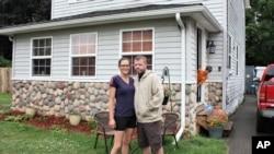 Kristal i Kris Martin ispred kuće, a jedno od šestoro dece viri kroz vrata (Foto: AP/Tammy Webber)