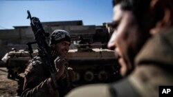 ທະຫານ ອີຣັກ ຄົນໜຶ່ງຖືປືນກົນ ໃນເວລາເດີນທາ ງໄປແຖວໜ້າໃນເມືອງ Mosul, ອີຣັກ, 6 ທັນວາ, 2016.